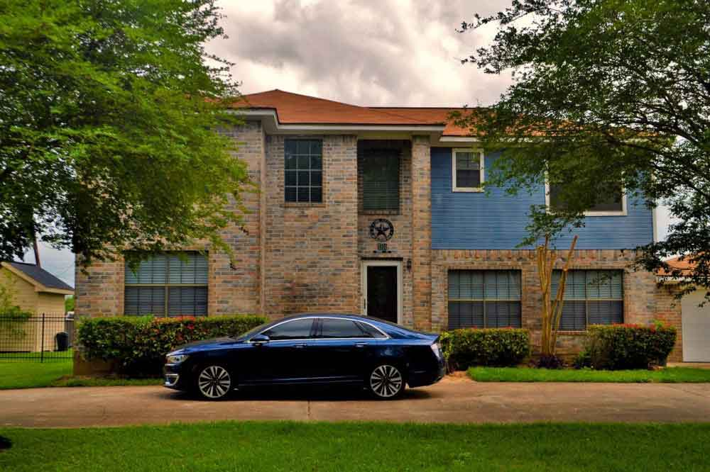 house with blue car in front