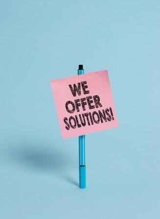 Blue pen holding pink we offer solutions note